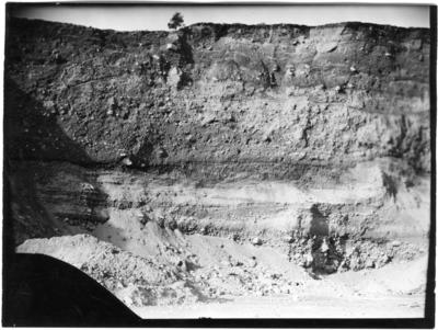 'Översiktsbild över vägg i grustaget. Bildtext: ''Dösebacka, södra delen av väggen i södra grustaget där mammutbeten hittades 1931. Fig. 1. Söder till vänster i bilden och norr till höger i bilden.'' ::  :: Ingår i serie med fotonr. 7058:1-32.'