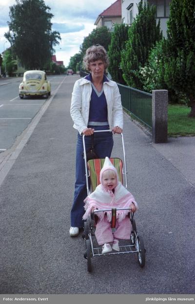 Yvonne Jonsson går, med en liten flicka i en sulky, på trottoaren utmed Tegnergatan i Huskvarna.
