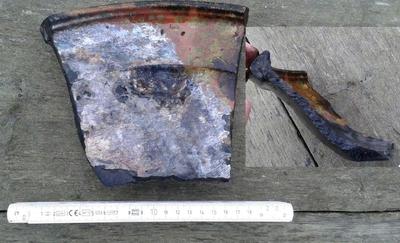 Fragment av en skål i yngre rödgods (1700-tal) i kulturlagret, hamnanläggningen Nacka 277.  Artefakten bärgades, dokumenterades och återdeponerades därefter (nära RAÄ Nacka 275). (Svindersviken, Nacka).