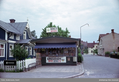 Kungskiosken i Huskvarna. Öppettiderna är på vardagar kl 6,30-21 och helgen 9-21. På taket sitter en skylt med reklam för Banco drycker. I bakgrunden syns Centralbageriet och en del av Husqvarna AB.