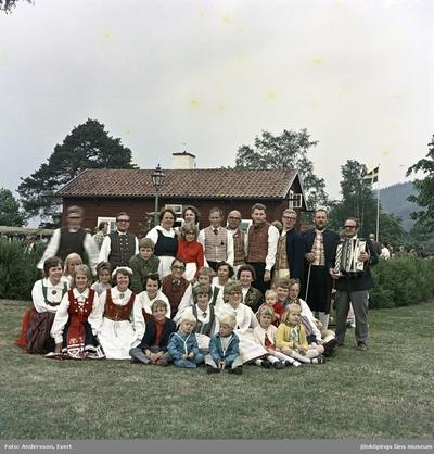 Vid Kroatorpet i Huskvarna är det fest på Midsommardagen och medlemmar från Huskvarna folkdanslag och Folkdansgillet Wätterringen har ställt upp sig för fotografering efter dansuppvisningen.