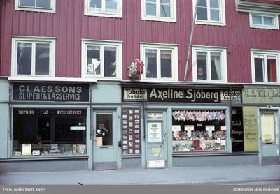 En del av Barnarpsgatan, en affärsgata i Jönköping. Här finns bland annat Axeline Sjöbergs Tobakshandel och Claessons Sliperi & låsservice. På våningen ovanför har SSU Wätterstad sina lokaler och en skylt i fönstret uppmanar till att stödja Chiles folk.