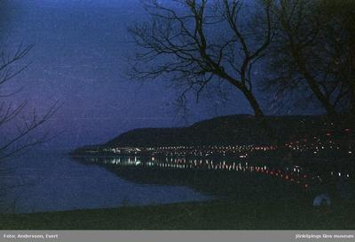 En nattbild tagen från stranden vid Vättersnäs utanför Huskvarna. E4:ans vägbelysning speglar sig i Vätterns vatten förbi Norrängen mot vista kulle.