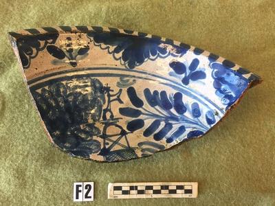 Skål med invändig vit tennglasyr och blå dekor, antagligen från 1700-talet. Möjligen tysk tillverkning då leran är mer ljusbrun än röd. (RAÄ Stockholm 206:1).