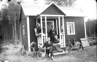 80aa6c24a7b5 Unga kvinnor och män med cyklar utanför mindre hus.