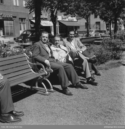 Tre herrar Jakobsson, Sandberg och Bohm sitter på en parkbänk på Esplanaden i Huskvarna.