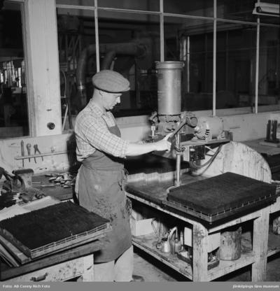 Penselmakare Lennart Ödman står och arbetar vid en maskin på Huskvarna borstfabrik.
