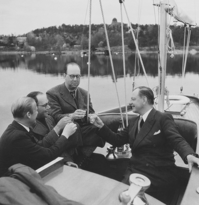 Gösta Åhlén tredje personen från vänster, Roy Hähnel längst till höger i segelbåt med en flaska konjak.