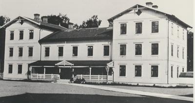 Karlsborg.  Infanterivolontärskolan , senare rekrytskolan för infanteriets officers-och reservofficersaspiranter.Befälsbyggnaden i början av 1880-talet medpunchveranda.Vid denna tiden dränerades gården ovh sten-trottoarer anlades och en vattenledning  från fästnineen inleddes. I Byggnaden:våning 1: Kassaförvaltningen, väbelns expedition, officersmässen, rum för officerare. Våning 2: Chefsexpedition, dagofficerens rum, rum för officerare. Våning 3:Vapen-och kasernunderofficersexpedition, idrottsexpedition, arkiv, rum för officerare och officersmässens betjäning.