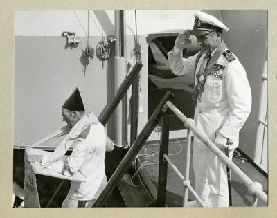 Bilden föreställer två män under ceremonierna kring ett linjedop ombord på minfartyget Älvsnabben i samband med långresan 1966-1967. En av männen är klädd i vit uniform och gör honnör. Den andra mannen, Oskar Linde, är klädd i en utklädnad.