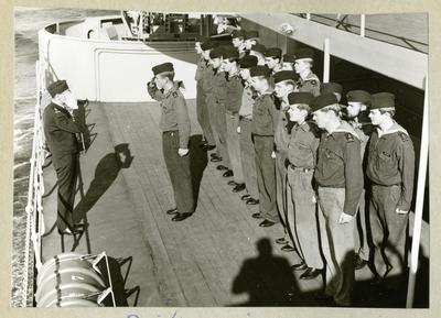 Bilden föreställer uniformsklädda besättningmän uppradade på däck ombord på minfartyget Älvsnabben. Två män står mittemot varandra och göra honnör. Bilden är tagen under långresan 1966-1967.