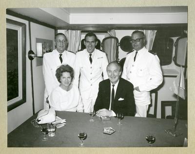 Bilden föreställer tre män i uniform, en man i kostym och en kvinna som poserar inför en gruppbild. Bilden är tagen i samband med minfartyget Älvsnabbens långresa 1966-1967.