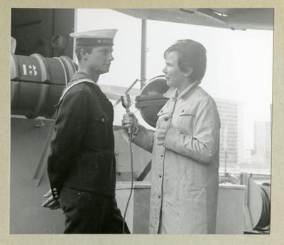 Bilden föreställer en kvinna med en mikrofon som intervjuar Carl XVI Gustaf, som står klädd i uniform. Bilden är tagen under minfartyget Älvsnabbens långresa 1966-1967.