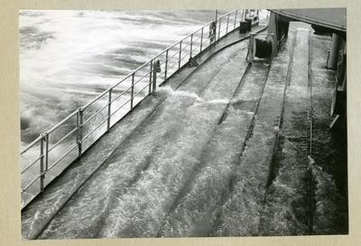 Bilden föreställer minfartyget Älvsnabbens däck fyllt med vatten till följd av stormigt vatten i samband med orkanen Diana. Bilden är tagen under fartygets långresa 1966-1967.