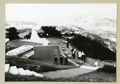 Bilden föreställer ett landskap med kullar och dalar. Vid en gräsplätt syns en rad bänkar, två bussar och uniformsklädda män. Bilden är tagen under minfartyget Älvsnabbens långresa 1966-1967.