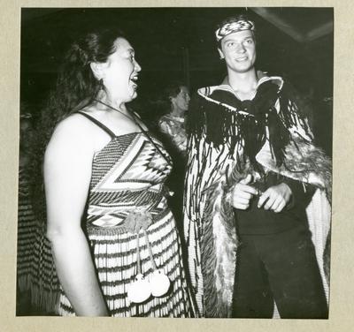 Bilden föreställer en kvinna i klänning och Carl XVI Gustaf som är utsmyckad med ett huvudband och en mantel med fransar. Bilden är tagen under minfartyget Älvsnabbens långresa 1966-1967.