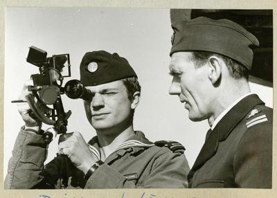 Bilden föreställer Carl XVI Gustaf och Oskar Linde under minfartyget Älvsnabbens långresa 1966-1967. På bilden använder Carl XVI Gustaf en sextant medan Oskar Linde står bredvid, båda iklädda uniform.