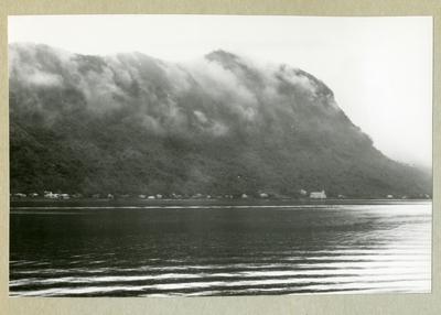 Bilden föreställer ett landskap med vatten och ett trädbeklätt berg. Bilden är tagen under minfartyget Älvsnabbens långresa 1966-1967.