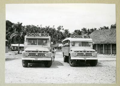 Bilden föreställer två skolbussar framifrån. I bakgrunden syns viss bebyggelse samt växtlighet med palmer. Bilden är tagen under minfartyget Älvsnabbens långresa 1966-1967.