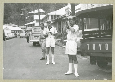 Bilden föreställer två bestättningsmän i vita sommaruniformer på en gata med fordon och bebyggelse. Bilden är tagen under minfartyget Älvsnabbens långresa 1966-1967.