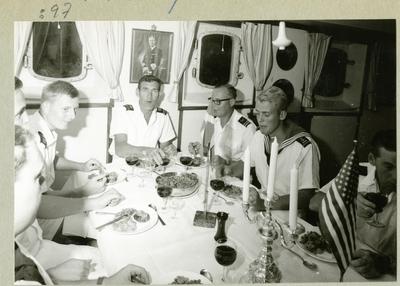 Bilden föreställer uniformsklädda besättningsmän som sitter till bords i minfartyget Älvsnabbens mäss för att förtära en middag. Bilden är tagen under fartygets långresa 1966-1967.