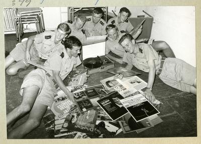 Bilden föreställer sju uniformsklädda besättningsmän ombord på minfartyget Älvsnabben, vilka ligger på golvet i spisarhörnan med en hög vinylskivor och lyssnar på musik. Bilden är tagen under fartygets långresa 1966-1967.