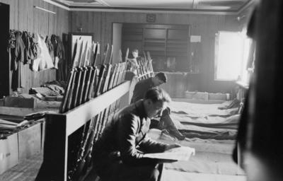 Interiör av en manskapsbarack vid F 19, Svenska frivilligkåren i Finland. Militärer, sovplatser och gevär.