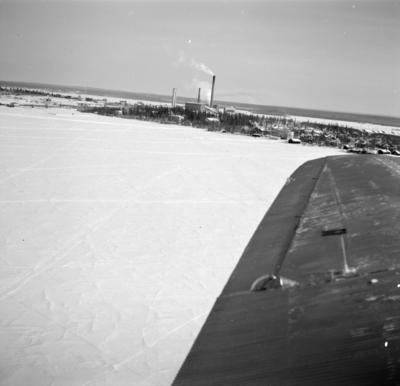 Flygfotografi av Veitsiluoto samhälle. Bild från F 19, Svenska frivilligkåren i Finland. Med flygplansvinge av flygplan Junkers F-13 i förgrunden.