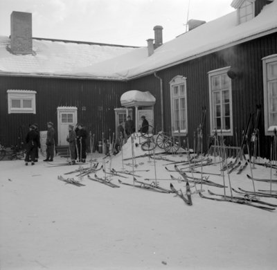 Skidparkering vid förläggning på F 19, Svenska frivilligkåren i Finland. En samling militärer vid huset.