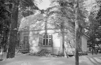 Ett hus i en dunge vid F 19, Svenska frivilligkåren i Finland, vintertid. Skidor står lutade mot huset och en vedtraven ligger bredvid.