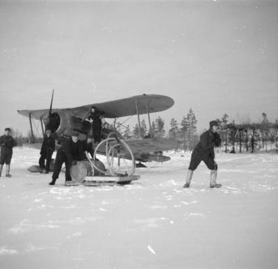 Tankning av flygplan Gloster Gladiator märkt gul G vid F 19 Ulriksbasen i Uleåborg, Svenska frivilligkåren i Finland. Sex flygmekaniker i arbete.