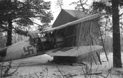 Flygplan Gloster Gladiator märkt gul I, tillhörande F 19, Svenska frivilligkåren i Finland, står med motorn i ett tält.