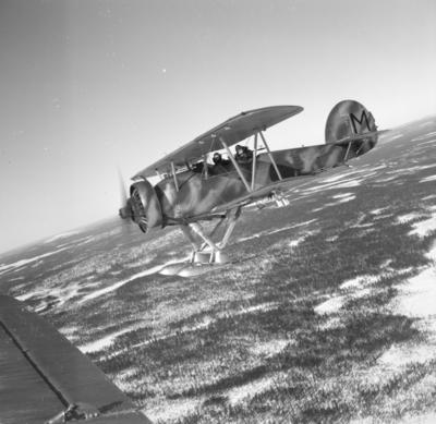 Flygplan Hawker Hart svar M Hämnaren vid F 19, Svenska frivilligkåren i Finland i luften över snöigt landskap. Två män i besättningen.
