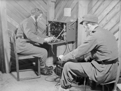 Radioavlyssning vid F 19, Svenska frivilligkåren i Finland. Två militärer vid radioapparat vid avlyssning av sovjetisk propaganda.