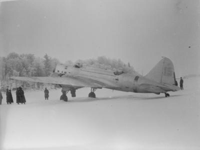 Sovjetiskt flygplan Iljushin DB-3 står på ett fält under finska vinterkriget, 1940. Människor i rörelse runtomkring. Vy bakifrån. Bild från F 19, Svenska frivilligkåren i Finland.