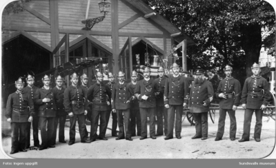 Gruppbild med brandsoldater framför den provisoriska brandstationen i Järnvägsparken. Brandchef Gustaf Hellgren står som 6:e från höger.