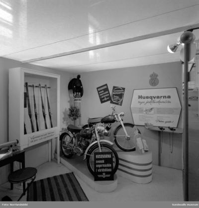 Husqvarnas monter i Läroverkets gymnastiksal på Sundsvallsmässan 1955.  Bland annat visas mopeder, vapen och symaskiner.