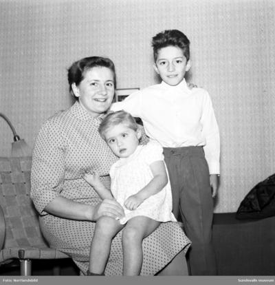 Familjen Karo som kommit som flyktingar från Ungern 1956 är en av tre familjer som fortfarande bor kvar i flyktinglägret i Bergeforsen 1958. På bilden mamma Irma med tvååriga Eva i famnen samt storebror Tibbi. Vid fototillfället saknades pappa Bela och äldsta dottern Mariana. Reportagebilder för Dagbladet.