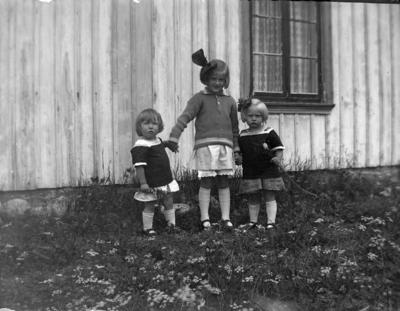 Tre barn framför bostadshus.