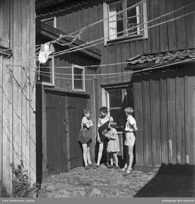 En bakgård i Jönköping. Fyra barn står och pratar, två bär en tidningsväska med AT tryckt på sidan.
