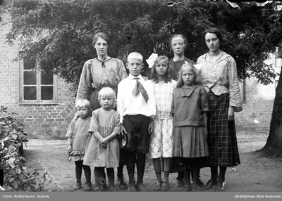 Tre kvinnor och fem barn står vid ett träd framför ett tegelhus.