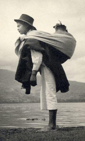 Otavalointiaaninainen  kantamassa isoa ruukkua selässään.