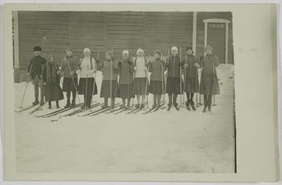 Sairalan kyläosaston lottia lähdössä hiihtämään valvojan kanssa Sairalan nuorisoseurantalolta