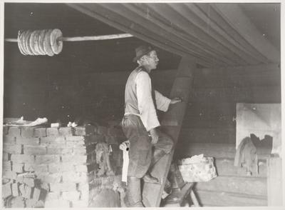 mies kattoparsille johtavan pölkkyrapun askelmilla Mäenpään savupirtissä