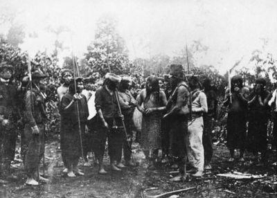 Jívaro-intiaanien voitonjuhla Einsupani: voittaja lähestyy taloa aseistetussa juhlasaatossa