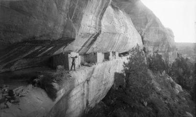 Chapin's mesa, Navajo Canyon, Little Long House. Kanjonin seinämässä sijaitseva pieni linnoitus, jossa useita matalia kallioasumuksia peräkkäin. Kuvattuna pohjoisesta päin. Ensimmäisen kallioasumuksen vierellä seisomassa Richard (?) Wetherill