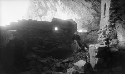 Chapin's mesa, Mountain Sheep Canyon (Rock C.), raunio 16? Al Wetherill istumassa osittain esiin kaivetussa kivassa, jonka seinässä pyöreä ikkuna-aukko. Oik. kallioasumuksen seinää, jossa suorakaiteen muotoinen aukko alavahvistuksineen