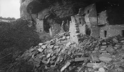 Chapin's mesa, Spruce Canyon, Spruce Tree House. Kallioasumuksen luoteispää, takana vas. korkea muuri, josta oikealle huoneet 79-71. Etualalla runsaasti irtonaisia rakennuslohkareita, taustalla kallionkielekkeen alustaa. Vas. pensaikkoa.
