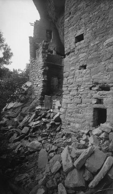 Chapin's mesa, Spruce Canyon, Spruce Tree House. Kallioasumuksen luoteispää, jossa kauimpana vas. korkea muuri ikkuna- ja oviaukkoineen. Edessä oik. lähes kallionkielekkeen kattoon ulottuva huone, jossa matala oviaukko ja useita ikkunoita