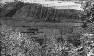 Wetherill's mesa, Mountain Sheep Canyon (Rock C.), raunio 17 - Jug House. Kallionkielekkeellä sijaitseva matala, ikkunaton kallioasumus, jossa vas. kolmen huoneen yhdistämä, oik. yksinäinen huone, joka ulottuu lähes kallionkielekkeen kattoon